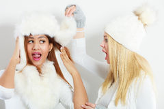 Two girls in winter clothing whispering secret Royalty Free Stock Photo