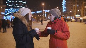Two girls in the center of the Christmas decorated city, drinking coffee and having fun. stock footage