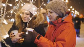 Two girls walk around the city on a winter evening acquire on the town square or coffee in tea cups and admiring the stock footage