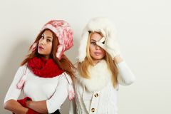 Two girls with winter outfit. Fashion winter people concept. Two girls with winter outfit. Attractive women wearing fur caps Stock Photo