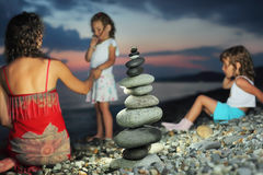 Two girls and woman sitting on stone seacoast Stock Image