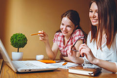 Two girls work at office on computer and tablet royalty free stock photo