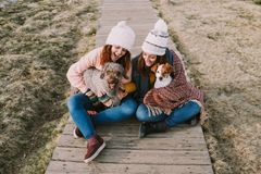 Two girls are wrapped in a blanket while playing with their dogs in the meadow stock images