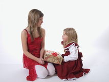Two girls with Xmas present. Older and younger sister holding wrapped Christmas present, white studio background Stock Photos