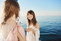 Two girls on yacht sailing in sea, having conversation about their great plans for vacation. Happy adult woman talks to. Two girls on yacht sailing in sea Stock Photography