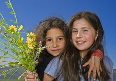 Two girls and yellow flowers. Two girls hugging and holding bouquet of wild yellow flowers Royalty Free Stock Photo