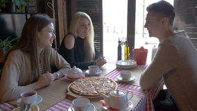 Two girls and a young man talking in a cafe sitting at a table. They drink tea and eat pizza. They tell the news, they. Smile. Good mood stock footage