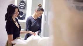 Two-girlsfriends choose dress. Two young woman chooses wedding gown at bridal store stock footage