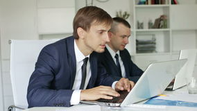 Two glad business male assistants. Wearing formalwear working together using laptops in company office stock video