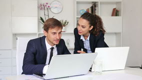 Two glad business male and female. Assistants wearing formalwear working using laptops in company office stock footage