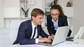 Two glad business male and female assistants. Wearing formalwear working using laptops in company office stock video footage