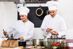 Two glad female and male young cooks stock images
