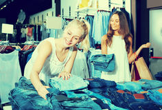 Two glad girls choosing denim trousers Stock Photo
