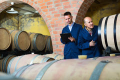 Two glad men winery employees writing note Stock Images