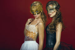 Two glam gorgeous women, blonde and brunette, in golden and bronze masks wearing evening gowns Stock Image