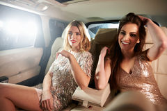 Two glamorous women relax in the back of a limo, in-car view Stock Photos