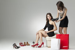 Two glamorous women trying high heels. Two glamorous women shopping high heels Stock Photography