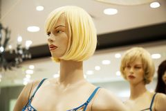 Two glamour blonde mannequins in a shopping mall. Cruel bitchy woman hatching up revenge behind friend`s back Stock Images