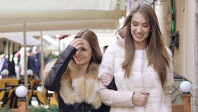 Two glamour girls walking in furry coats in shopping center. Slowly. Two happy girls walking in furry coats in shopping center. Slowly stock video