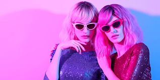 Two Glamour woman in fashion neon light. Party. Two women in Party bright luxury outfit. High Fashion. Model girl with pink blonde dyed hair, makeup. Colorful stock images