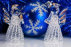 Two glass angel and Christmas tree tinsel. Two decorative glass angel, blue christmas ball and Christmas tree tinsel on white with reflections stock photos