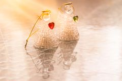 Two glass angels with hearts on the table. Warm sunshine. Copy space. Peace concept stock image