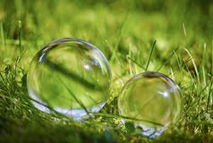 Two glass balls on the grass in the summer Stock Images
