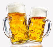 Two glass beer mugs full of golden lager Royalty Free Stock Photography