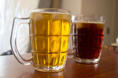 Two glass of beers. View of two glass of beers. One dark and one gold royalty free stock photos