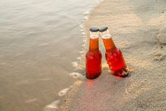 Two glass bottles of cherry beer on the sand with flowing water all around.  Royalty Free Stock Images