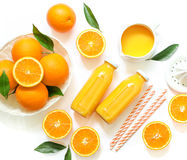 Two glass bottles of fresh orange juice, straws and oranges isolated on white background top view. Royalty Free Stock Photo