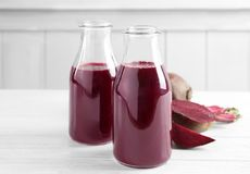 Two glass bottles with fresh smoothie and beets. On wooden table Stock Photo