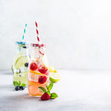 Two glass bottles with lemonade. From fresh citrus lemon, raspberries, blueberries, lime and mint with drinking straws. Healthy summer beverage. Copy space Stock Photo