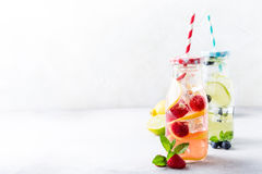 Two glass bottles with lemonade. From fresh citrus lemon, raspberries, blueberries, lime and mint with drinking straws. Healthy summer beverage. Copy space Royalty Free Stock Image