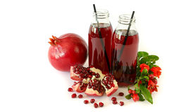 Two glass bottles of pomegranate juice, fruit, seeds and flowering branch of pomegranate tree isolated on white.