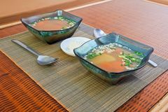 Two glass bowls with vegetable soup and a saucer with sour cream Stock Image