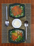 Two glass bowls with vegetable soup and a saucer with sour cream Royalty Free Stock Photos