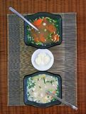 Two glass bowls with vegetable soup and a saucer with sour cream Royalty Free Stock Photography