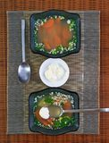 Two glass bowls with vegetable soup and a saucer with sour cream Stock Photo