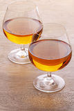 Two glass with brandy. On the wooden table Royalty Free Stock Photos
