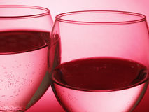 Two glass with bubble. Water in two glass isolated on red background Stock Images