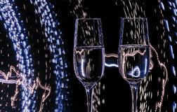 Two glass of champagne wine on background of abstract colored lights in motion Royalty Free Stock Photos