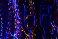 Two glass of champagne wine on background of abstract colored lights in motion Stock Image