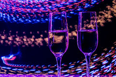 Two glass of champagne wine on background of abstract colored lights in motion Stock Photography