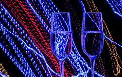 Two glass of champagne wine on a background of colored lights in motion Royalty Free Stock Photography