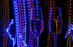 Two glass of champagne wine on a background of colored lights in motion Stock Photo