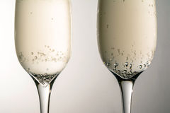 Two glass of champagne wine close up, bubbles, on grey background Royalty Free Stock Images