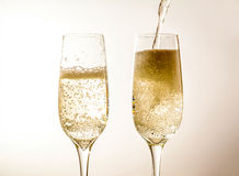 Two glass of champagne wine close up, bubbles, on grey background Stock Photos