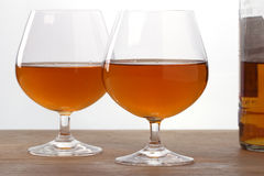 Two glass with cognac. And bottle on the wooden table Stock Photos