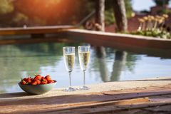 Two glass of cool champagne wine with a plate of strawberries outdoors in a pool side terrace in a sunny summer afternoon royalty free stock photography